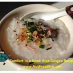bowl of congee with toppings in a cream colored bowl, with a chinese soup spoon on the side
