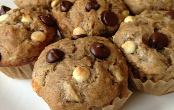 banana chocolate chip muffins on a plate with bananas in the background