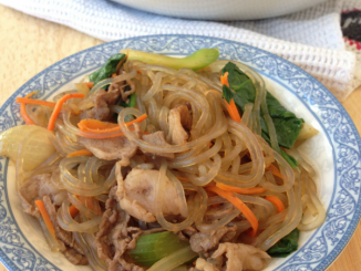 small blue and white plate containing delicious beef japchae