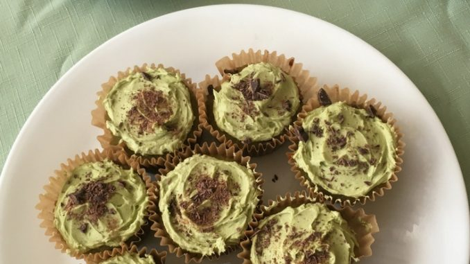 A plate of Matcha Chocolate Chip Cupcakes with a cup of green tea and a teapot