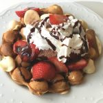Bubble Egg Waffle Sundae piled high with ice cream, sliced strawberries, whipped cream, and chococlate sauce drizzle. #nutfree #dessert