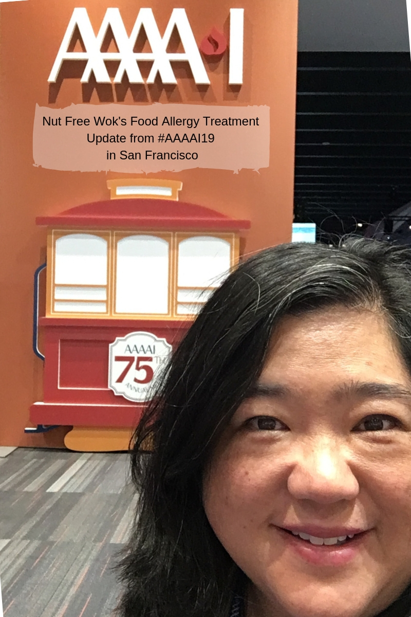 Sharon Wong from Nut Free Wok standing in front of #AAAAI19 sign with a cable car