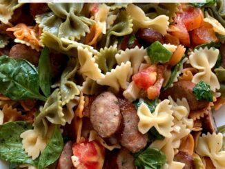 a platter of rainbow bowtie pasta with tomatoes, brie, and sausages