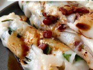 close up of rice noodle rolls with a drizzle of sweet soy sauce on a grey plate
