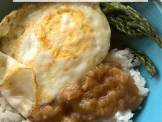 Dairy-free beef gravy over rice, served with an over easy egg and roasted asparagus in a blue bowl