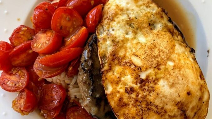 Rice topped with hamburger patty, gravy, egg, and tomatoes on a white plate.